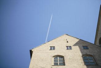 Bild av husvägg samt flygplan som flyger förbi i himlen