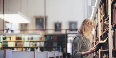 Studerande som läser bok i biblioteket