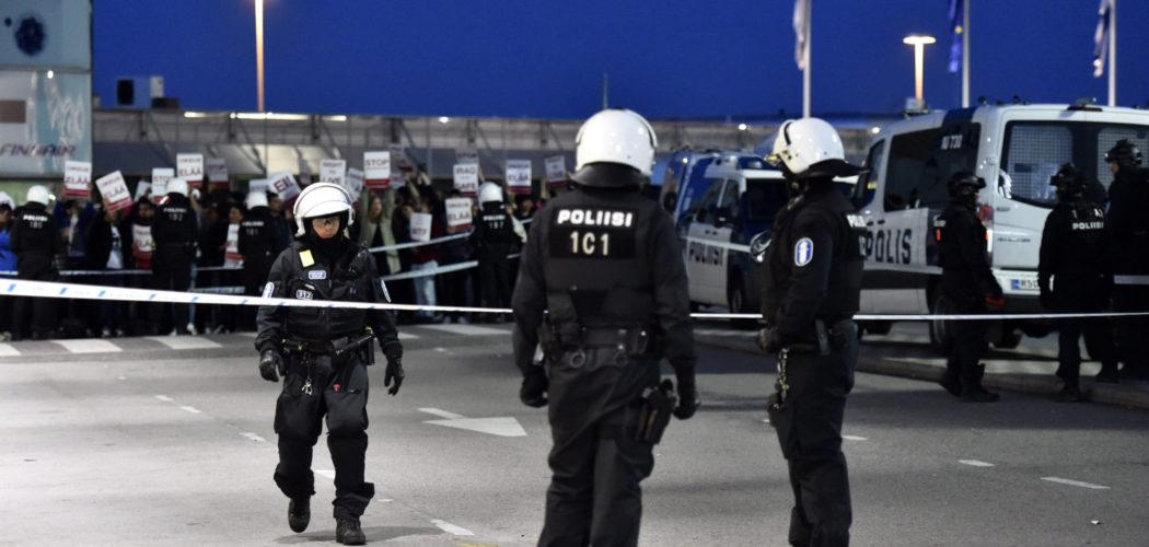 Tre poliser i skyddsutrustning med en demonstrerande folkmassa i bakgrunden.