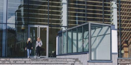 Två studerande på trappan till Academill.
