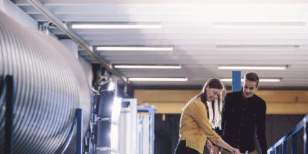 Bild på studerande som står vid en dator