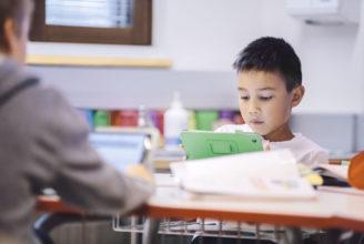 Bild på en liten pojke som sitter vid ett bord och spelar på sin tablet