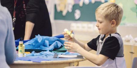 Bild på en liten pojke som pysslar vid ett bord