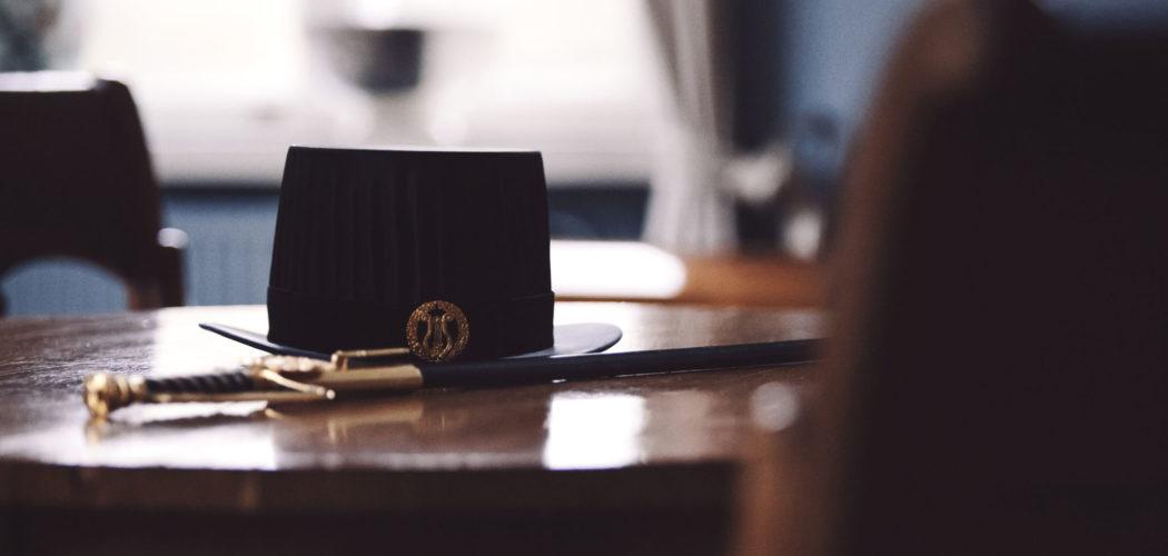 En doktorshatt och -värja på ett bord