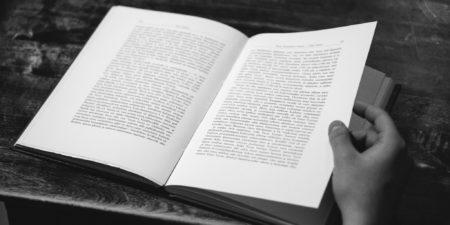 uppslagen bok, hand som bläddrar