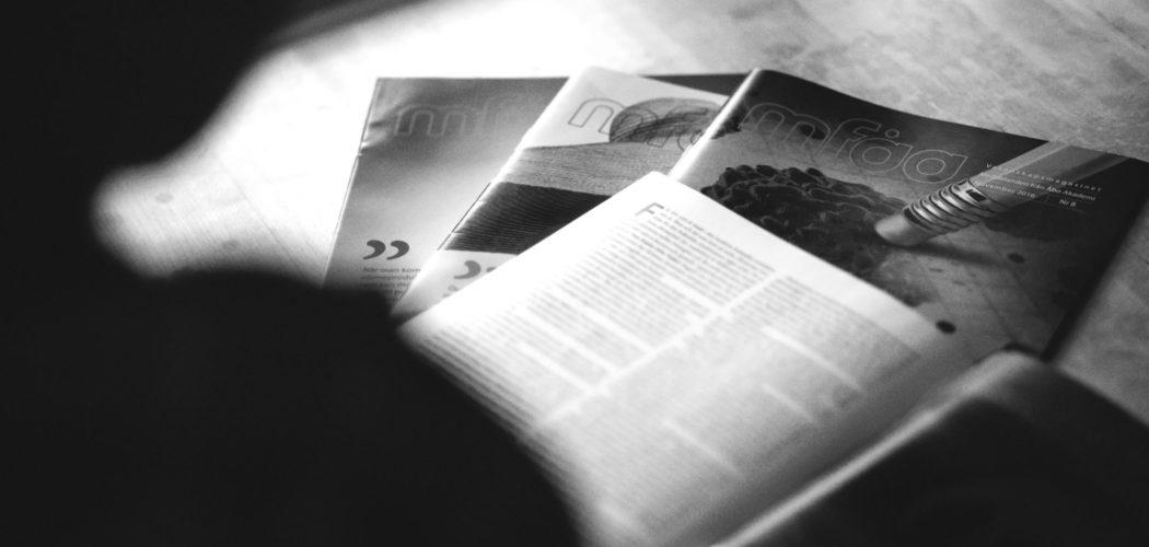 svart-vit bild på uppslagna tidningar
