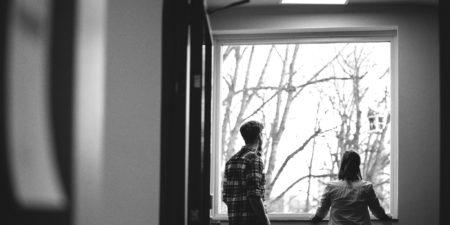 Två studenter vid ett fönster.