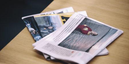 Tre dagstidningar på ett bord.