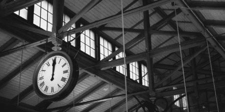 stor klocka hänger i ett tak, svartvit bild