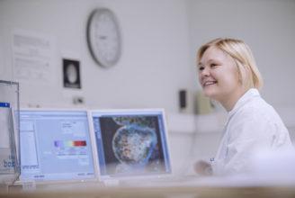 Studerande som sitter vid en datorskärm och studerar celler.