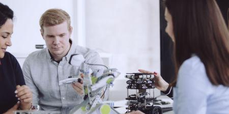 Studerande som sitter med en robot