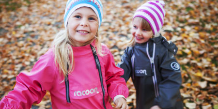 Två barn som leker med löv.