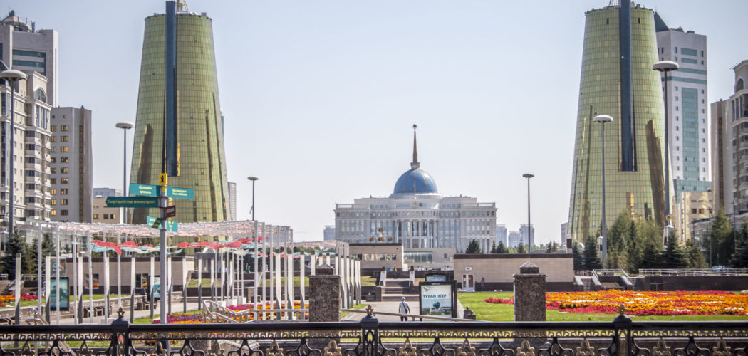 Vy över presidentpalatset i Kazakstan med en gul- och rödblommig parkmiljö i förgrunden och stora torn på sidorna.