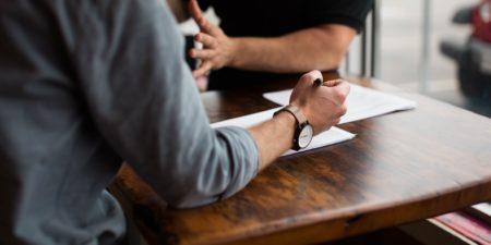Bild på två personer som diskuterar vid ett träbord