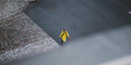 Person som går utomhus i gul regnkappa.