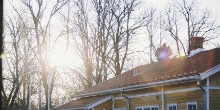 Gult hus i Åbo med solljus mellan trädtopparna.