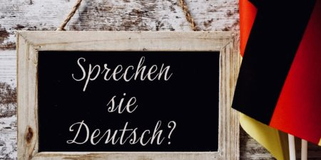a wooden-framed chalkboard with the question Sprechen sie Deutsch? do you speak German? written in German, and some flags of Germany against a rustic wooden background