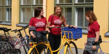 Tre studerande med en gul cykel.