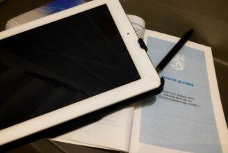 En iPad, en bok med Finlands lag och en penna.