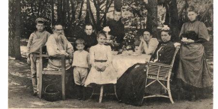 Svartvitt foto på Leo Tolstoj med familj. Sammanlagt nio personer i utomhusmiljö runt ett bord dukat med kaffe- eller teservis.