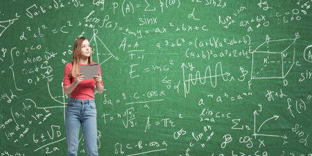 Young lady is pondering about complicated math problem. Formulas and graphs are drawn on the green chalkboard.
