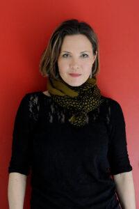 Psykolog Julia Korkman framför röd vägg.