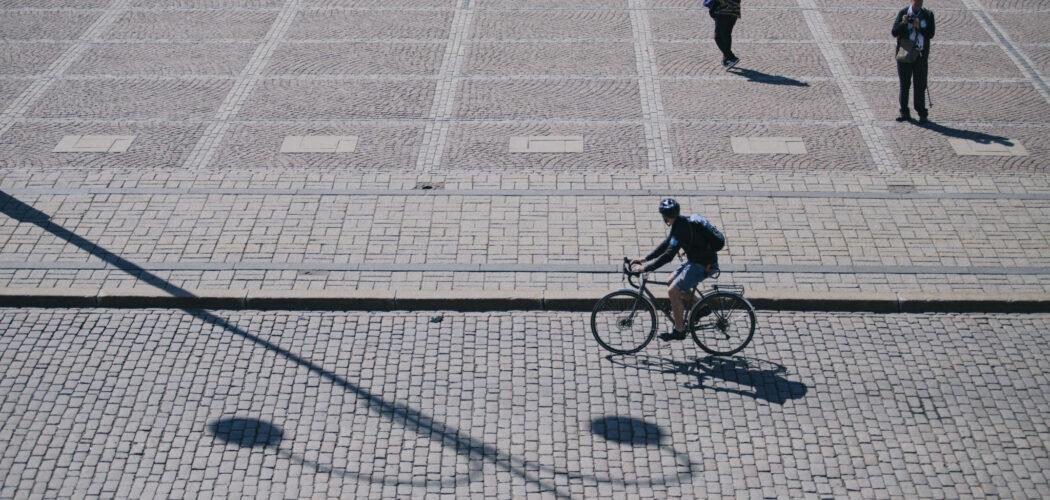 Cyklist cyklar på kullerstensgata.