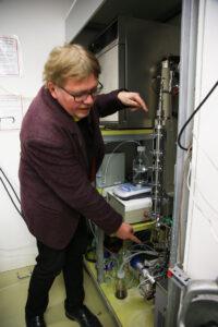 Professor Jyri-Pekka Mikkola står i laboratoriemiljö och pekar på reaktorns in- och utgång.