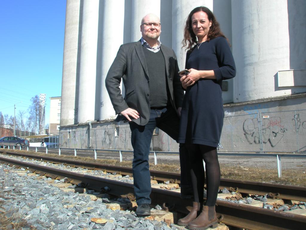 Peter Ehrström och Marina Lindell poserar vid järnvägsspår framför silorna bredvid Academill.