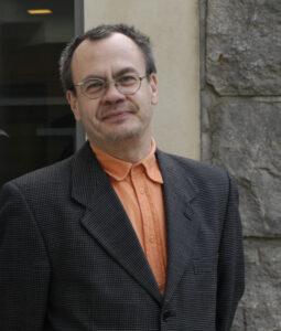Tapio Salmi i svart kavaj och orange skjorta