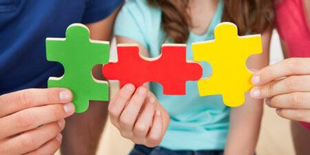 Bilden illustrerar pusselbitar i händerna på barn.