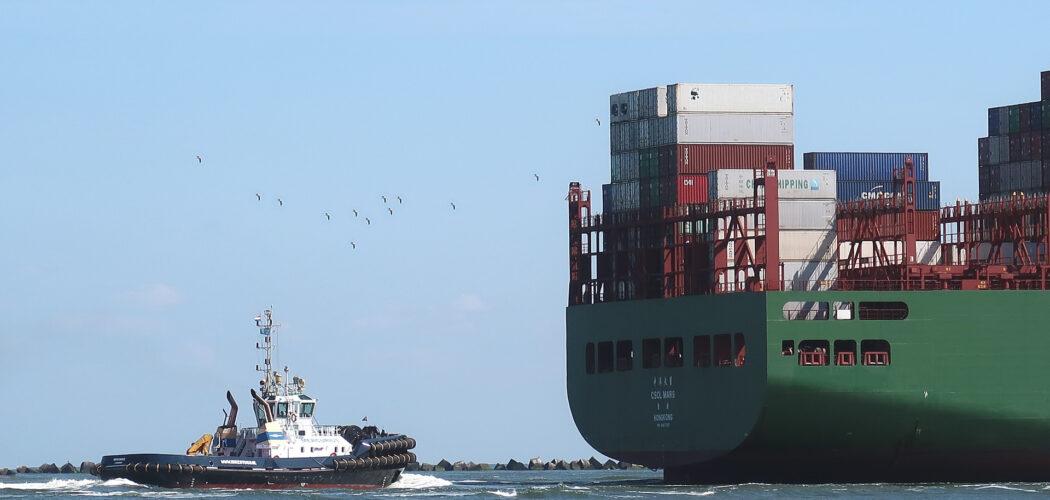 en bogserbåt och aktern på ett lastfartyg