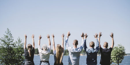 Studerande står på en rad med händerna i luften.