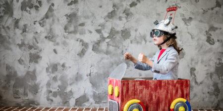 """Ett barn som sitter inne i en leksaksbil. Bild för """"Mer än en berättelse""""-projektet"""