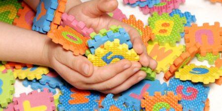 Barnhänder som håller i bokstavs- och sifferpusselbitar.