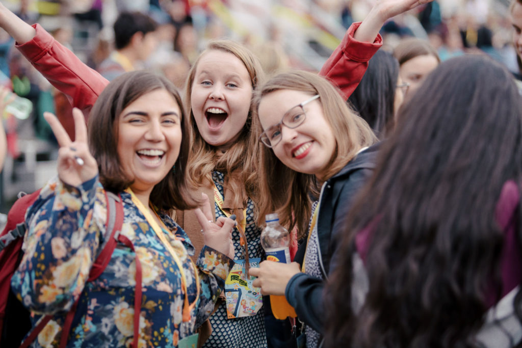Tre studerande som ler brett i kameran