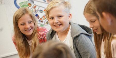 Bild på glada barn i klassrummet.