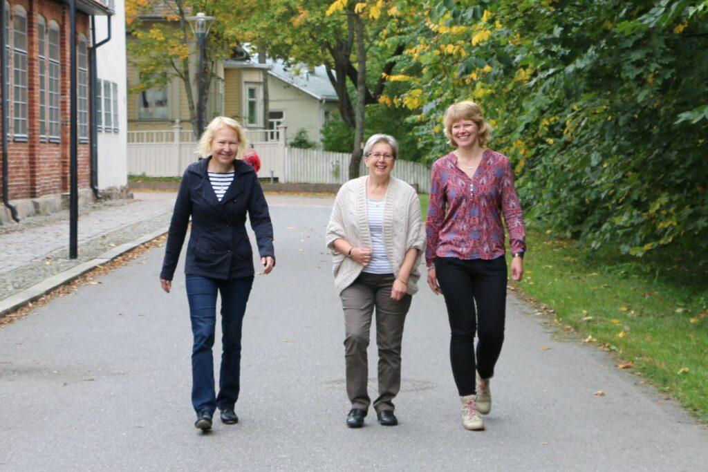 Tre glada kvinnor går i bredd.