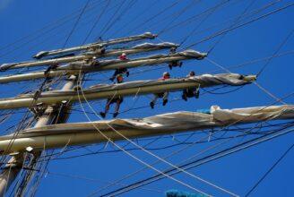 Flera personer klättrar i en enorm mast på segelskuta. Blå himmel som bakgrund.