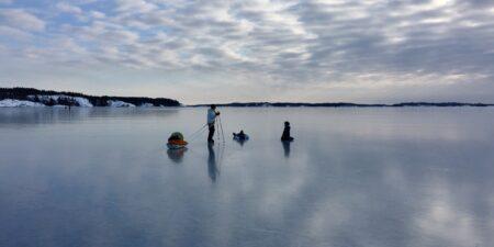 Några personer på spegelblank is med långfärdsskridskor och kälke