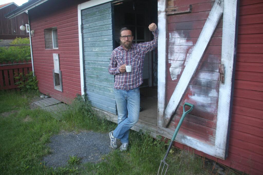 Kai Latvalehto med en kaffemugg i handen vid porten till ett rött uthus.