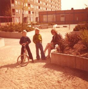 Förortsmiljö på 1970-talet. Två barn och en mamma på en grusgård framför ett höghus.