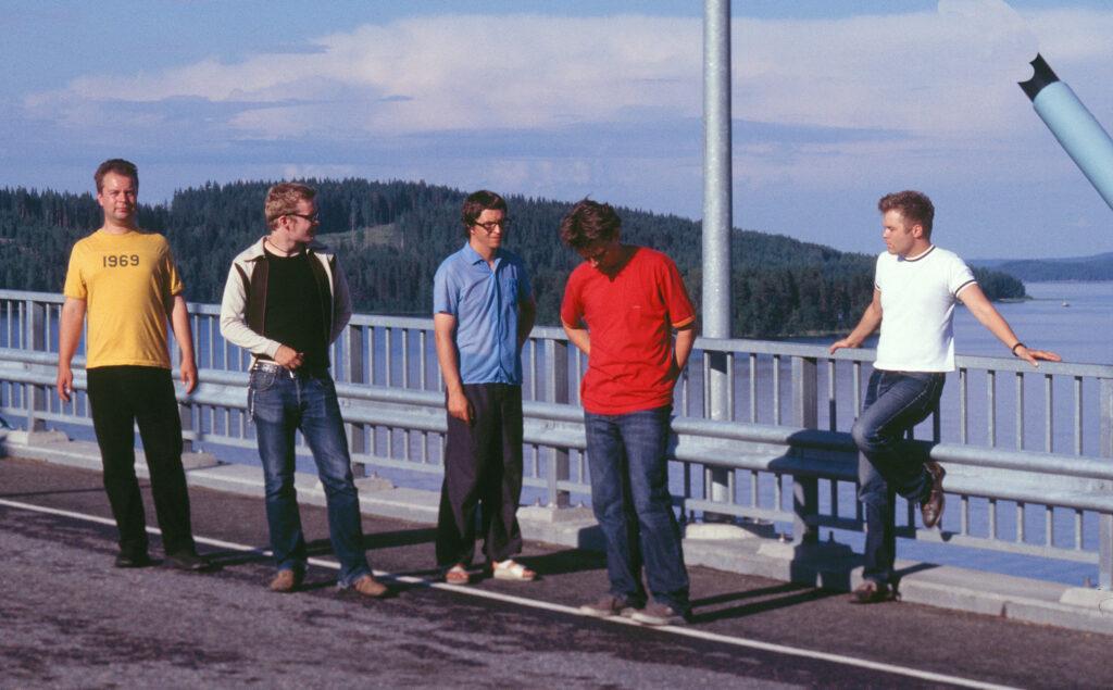 Foto på rockbandet Aknestik, fem män i färggranna skjortor på en bro.