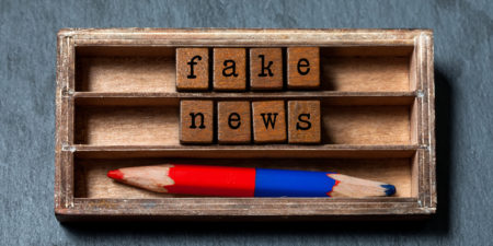 Fake news concept. Vintage box wooden cubes words phrase Fake News old style letters words, red blue pencil on gray stone textured background. Close-up, up view, soft focus.