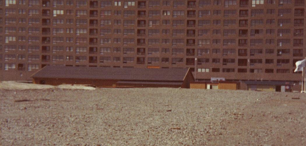 Bostadsområde på 1970-talet i Sverige, rödbrunt höghus med stort grusfält i förgrunden.