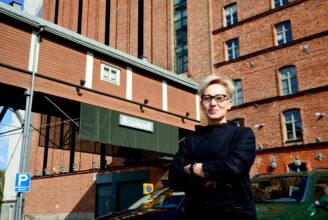 Professor Mia Porko-Hudd, står med armarna i kors framför Academill i Vasa, röd tegelbyggnad.