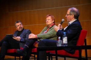 Göran Rosenberg talar vid panelen vid Imagine! medan Alf Rehn och Tarja Halonen lyssnar på hans vänstra sida.