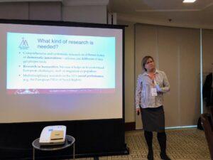 Professor elina Pirjatanniemi står med ett papper i handen bredvid en skärm upplyst av en Powerpoint-presentation.