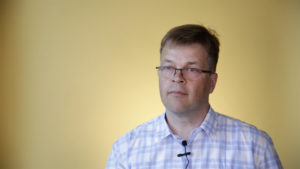 Ronald Österbacka i blåvitrutig skjorta, framför gul bakgrund.