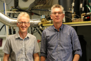 Professorerna Henrik Saxén och Ron Zevenhoven i laboratoriemiljö med rör i bakgrunden.